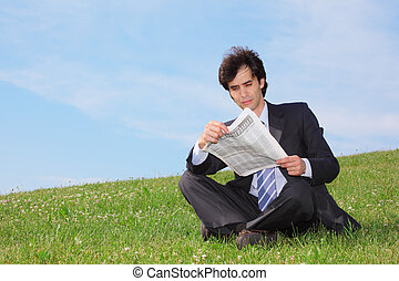 businessman sitting  on the meadow and reading newspaper