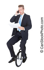 Businessman Sitting On Unicycle Talking On Cellphone Over...
