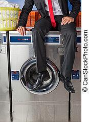 Businessman Sitting On Washing Machine - Low section of...
