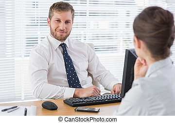 Businessman sitting with a co worker at his desk
