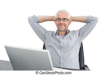 Businessman sitting with hands behind head and laptop