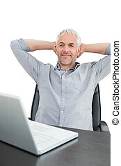 Businessman sitting with hands behind head with laptop