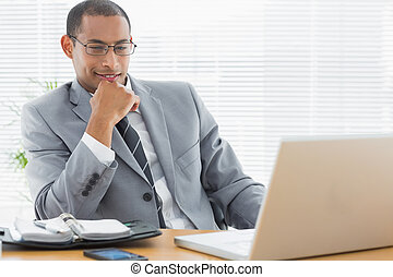 Businessman sitting with laptop at office desk