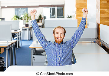 Businessman sitting with raised hands and celebrating success in office