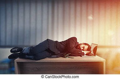 Businessman sleeping over a desk due to overwork -...