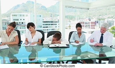 Businessman sleeping while colleagues are working