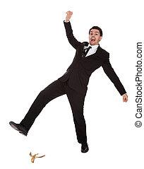 Businessman slipping on banana peel. Isolated on white