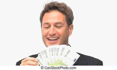 Businessman smelling his money against a white background
