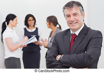 Businessman smiling and three businesswomen speaking