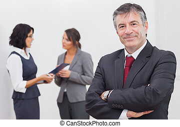 Businessman smiling and two businesswomen speaking