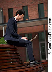 Businessman smiling and working on laptop outdoors