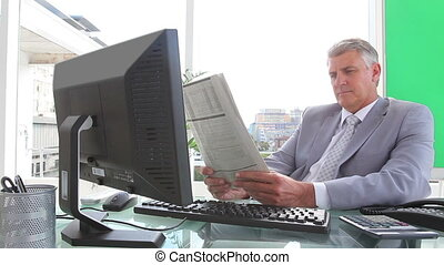 Businessman smiling as he reads a newspaper in an office