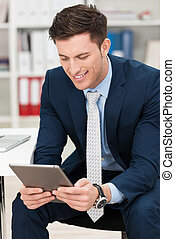 Businessman smiling as he reads his tablet screen
