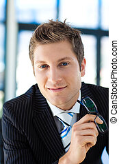 Businessman smiling at the camera holding glasses