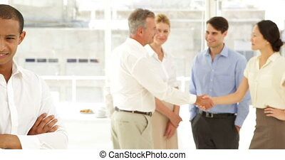 Businessman smiling in front of his staff