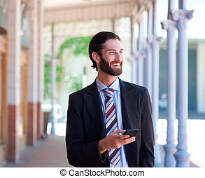 Businessman smiling outdoors with mobile phone