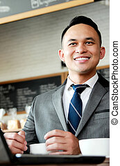 businessman smiling while working on his laptop