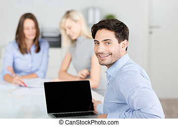 Businessman Smiling With Colleagues In Background At Desk