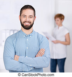 Portrait of confident young businessman smiling with female coworker reading document in background at office