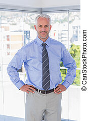Businessman smiling with hands on hips