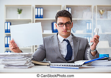 Businessman smoking at work in office holding a blank message bo