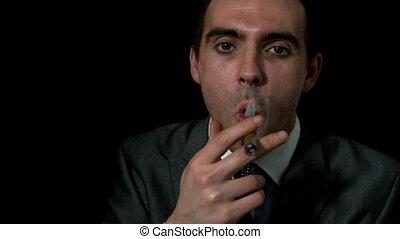 Businessman smoking his cigar on b