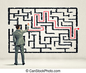 Businessman solving labyrinth problem - Back view image of...