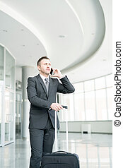 Businessman Speaking by Phone in Airport