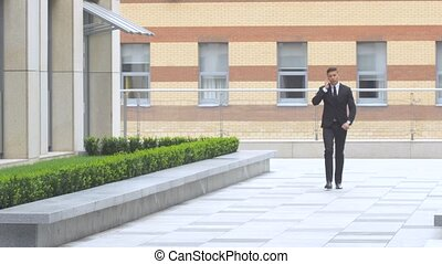 businessman speaking on the phone while walking along modern building
