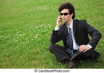 businessman speaks by phone sitting on grass