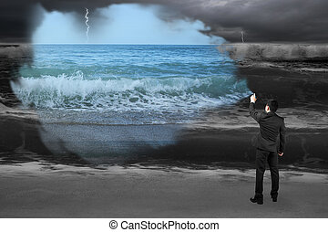 Businessman spraying calm sea paint covered dark stormy ocean