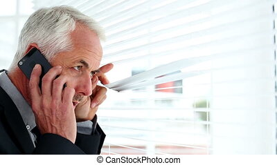 Businessman spying through blinds a