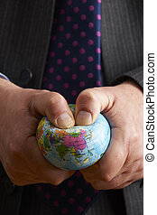 Businessman Squeezing Globe Over Asia