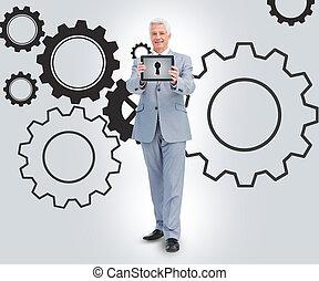 Businessman standing against a cogs background - Businessman...