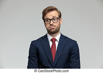 businessman standing and holding air in his mouth anxious