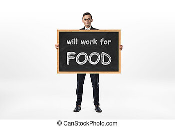Businessman standing and holding blackboard with words 'will work for food' written on it