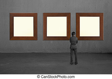 Businessman standing and looking at three blank wooden frames on concrete wall