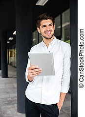 Businessman standing and using tablet outdoors