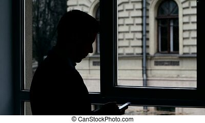 Businessman standing at the window, talking on phone discussing important details. Silhouette