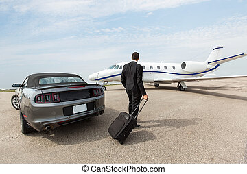 Businessman Standing By Car And Private Jet At Terminal - ...
