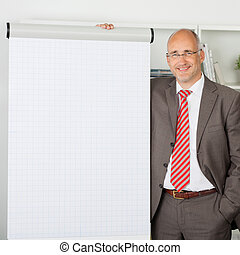 Businessman Standing By Flipchart In Office