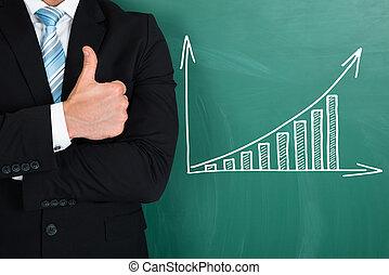 Businessman Standing By Graph Drawn On Chalkboard -...