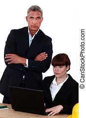 businessman standing close to his assistant