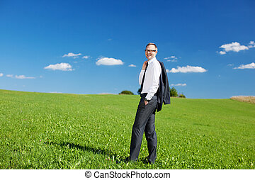 Businessman standing in a green field