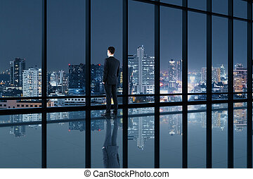 Businessman standing in contemporary office interior