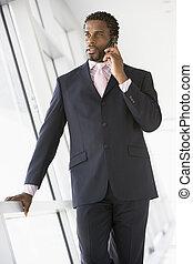 Businessman standing in corridor using cellular phone
