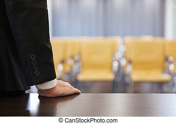 Businessman standing in empty meeting hall
