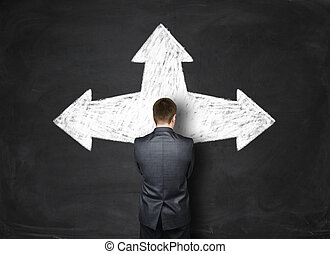 Businessman standing in front of a black wall with arrows pointing at different directions