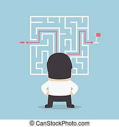 Businessman standing in front of a maze with a solution