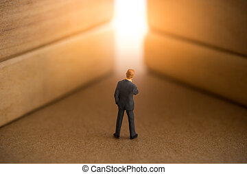 Businessman standing in front of bright light exit.